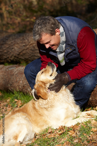 Man Taking Dog On Walk Through Autumn Woods