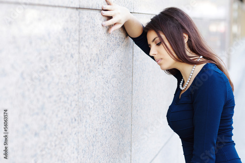 Portrait of tired businesswoman leaning at the wall