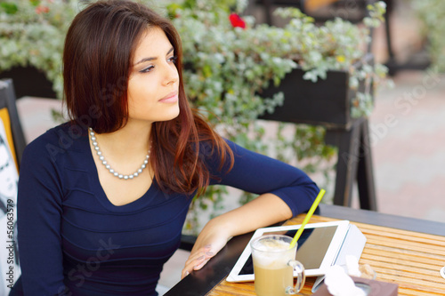 Elegant woman with tablet computer drinking coffee