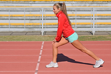 Attractive young woman doing stretching exercises on track