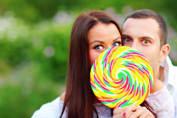 Young couple covering their faces with candy