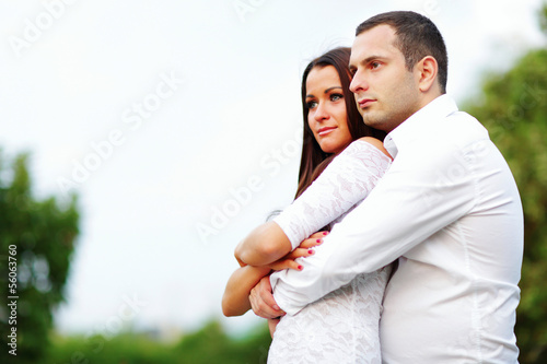 young romantic couple looking at copyspace outdoors