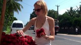 The girl buys a rambutans in a street market.