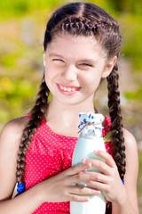 Девочка держит в руках бутылку молока