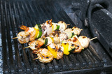 skewers of seafood grilling
