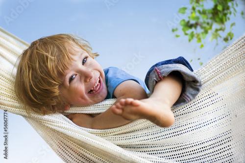 Leinwanddruck Bild Lachendes Kind in Hängematte