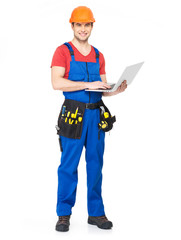 Young worker with  tools holds the laptop