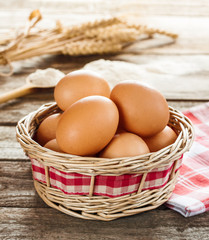 Eggs in a wicker basket on vintage planked wood table