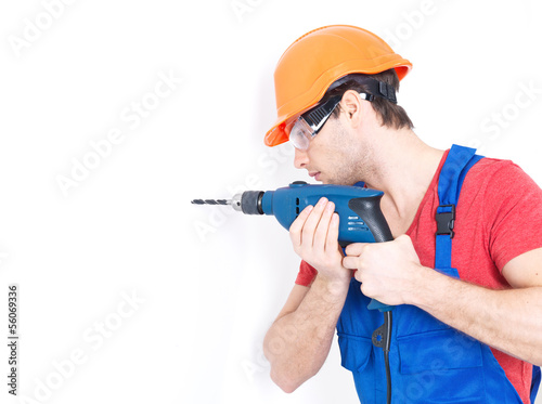 A man drilling a hole in the wall.