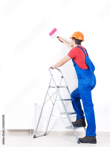 Craftsman painter stands on the stairs with roller