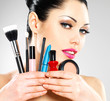Beautiful woman with makeup brushes