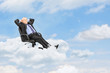 Mature businessman resting in armchair and floating on a cloud