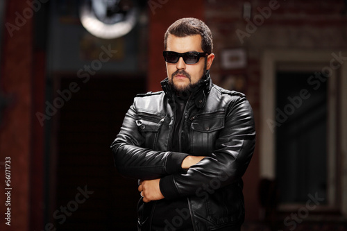 Man with glasses wearing black jacket and posing