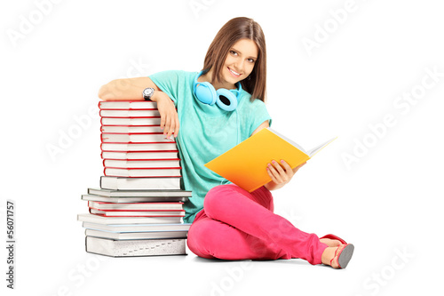 Smiling female student with headphones posing near many books
