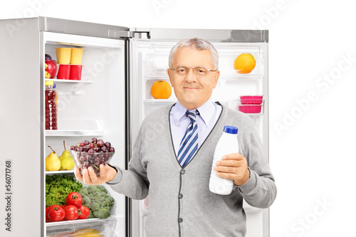 Mature man holding a bottle and grapes next to a fridge