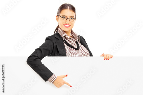 Smiling beautiful woman in suit pointing on a blank panel