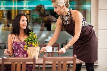 Hübsche Frau im Cafe wird von hübscher Kellnerin bedient