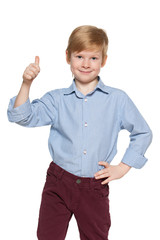 Cute young boy holds his thumb up