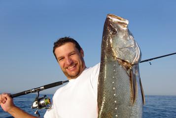 Pêcheur en mer tenant un  gros maigre (courbine)