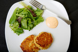 Crab Cakes and Salad on White Plate and Black Background