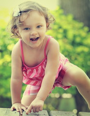 Small happy child girl climbing and looking in camera on summer