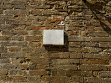 blank plaque on a brick wall surface.