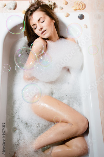 Portrait of young pretty woman sitting in bath with foam