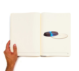 two CDs printed on white book.