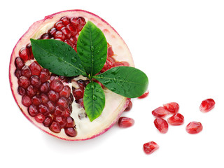 Pomegranate fruit with green leaves isolated on white background