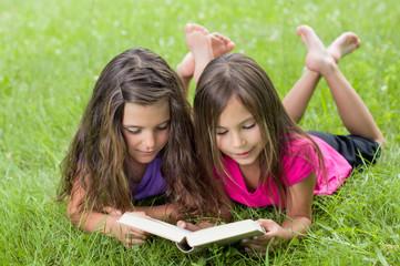 Zwei Mädchen lesen spannendes Buch