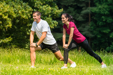 Female and male runner stretching outdoors
