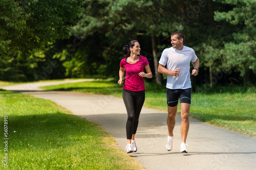 Cheerful couple friends running in park