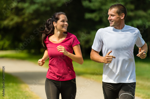 Cheerful Caucasian couple running outdoors