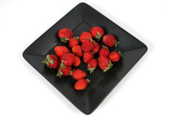 strawberries on Black Plate over White