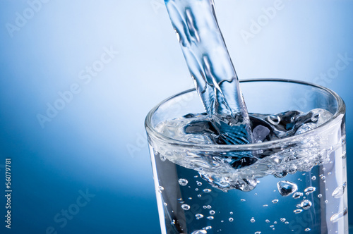 Papiers peints Eau Pouring water into glass on blue background