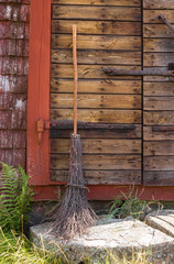 Broom at the entrance of a rustic house