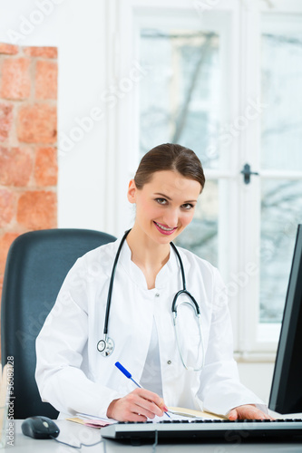 Female doctor writing in document