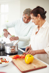 Senior Indian Couple Cooking Meal At Home