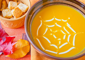 Pumpkin soup decorated with cream spider web