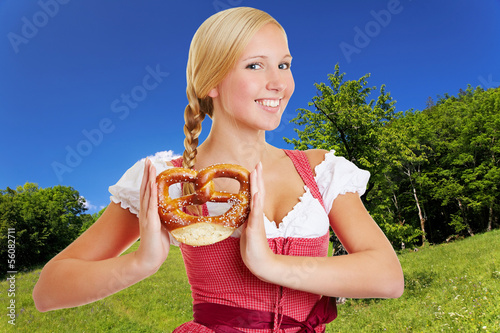 Woman in dirndl in bavarian landscape