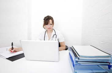 Young female doctor with laptop writing notes on desk in clinic