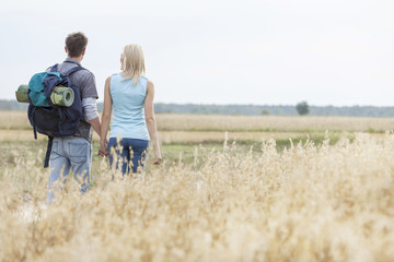 Rear view of young hiking couple walking through field