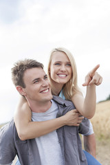 Beautiful woman showing something to man while enjoying piggyback ride at field