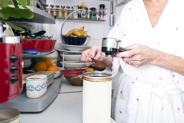 Midsection of senior woman filling ground espresso in portafilter at kitchen counter