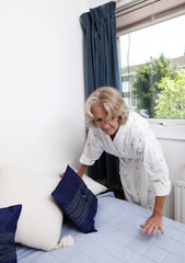 Senior woman arranging cushions on bed at home