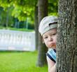 Little boy hiding behind tree