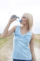 Young woman drinking water from bottle on field