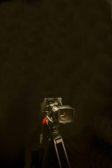 Digital camera and tripod against black background