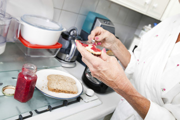 Cropped image of senior woman applying jam on toast in kitchen