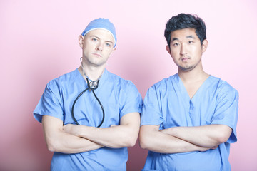 Portrait of two male surgeons standing with arms crossed over pink background